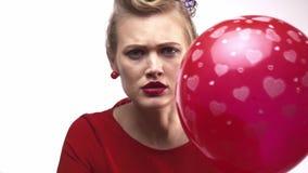 Η νέα ξανθή γυναίκα απειλεί να εκραγεί το μπαλόνι με μια βελόνα απόθεμα βίντεο