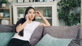 Η νέα όμορφη ασιατική γυναίκα καλεί το φίλο στο κινητό τηλέφωνο που μιλά και που χαμογελά στο καθιστικό στο σπίτι Σύγχρονες συσκε φιλμ μικρού μήκους