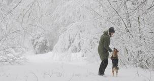 Η νέα όμορφη καυκάσια γυναίκα κοριτσιών έντυσε στο παιχνίδι σακακιών με το κουτάβι του μικτού σκυλιού φυλής στο χειμερινό δάσος σ απόθεμα βίντεο
