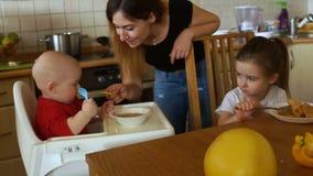 Η νοικοκυρά στην κουζίνα ταΐζει το γιο και την κόρη της για το γεύμα το λουλούδι ημέρας δίνει το γιο μητέρων mum φιλμ μικρού μήκους