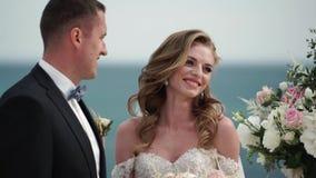 Η νύφη και ο νεόνυμφος στη γαμήλια τελετή Μια νεολαία συνδέει τις ερωτευμένες στάσεις στην αψίδα Γάμος θαλασσίως φιλμ μικρού μήκους