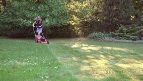 Η ξυπόλυτη γυναίκα έκοψε το λιβάδι με το θεριστή χορτοταπήτων στον πράσινο κήπο 4K απόθεμα βίντεο