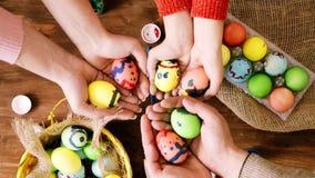 Η οικογένεια κρατά τα χέρια με τα χρωματισμένα αυγά πέρα από τον πίνακα με τα αυγά Πάσχας απόθεμα βίντεο