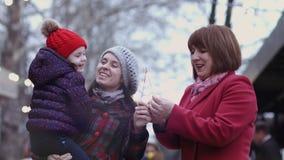 Η οικογένεια τριών γενεών των χαμογελώντας γυναικών που απολαμβάνουν το χρόνο μαζί και που κρατούν λαμπιρίζει οικογενειακά καρύδι απόθεμα βίντεο