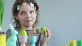 Η δημιουργικότητα των παιδιών, τα αυγά Πάσχας χρωμάτων κοριτσιών, λέρωσε τα δάχτυλά της στο χρώμα, χαμογελώντας χαρωπά οικογένεια φιλμ μικρού μήκους