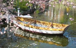 Η ρομαντική άποψη μιας ξύλινης βάρκας στην Κοπεγχάγη στη Δανία που περιβάλλεται θαλασσίως †‹â€ ‹ανθίζει σε μια μικρή λίμνη στοκ εικόνες