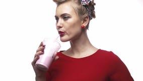 Η όμορφη γυναίκα στο κόκκινο φόρεμα πίνει το milkshake της σε σε αργή κίνηση απόθεμα βίντεο