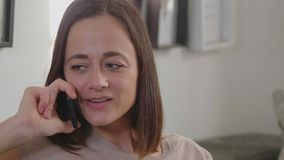 Η όμορφη γυναίκα παίρνει ένα τηλεφώνημα στο καθιστικό της απόθεμα βίντεο