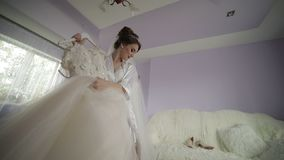 Η όμορφη και καλή νύφη στην εσθήτα νύχτας κρατά την κρεμάστρα με ένα γαμήλιο φόρεμα Γαμήλιο πρωί Αρκετά και καλά-καλλωπισμένη γυν φιλμ μικρού μήκους