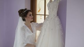 Η όμορφη και καλή νύφη στην εσθήτα νύχτας στέκεται κοντά στο γαμήλιο φόρεμα Γαμήλιο πρωί Αρκετά και καλά-καλλωπισμένη γυναίκα κίν απόθεμα βίντεο