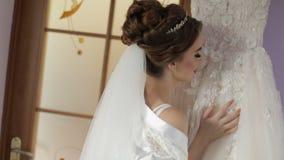 Η όμορφη και καλή νύφη στην εσθήτα νύχτας στέκεται κοντά στο γαμήλιο φόρεμα Γαμήλιο πρωί Αρκετά και καλά-καλλωπισμένη γυναίκα απόθεμα βίντεο