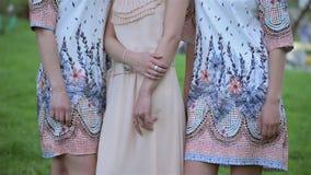 Η όμορφη φθορά νυφών και παράνυμφων ντύνουν και η στάση το ένα δίπλα στο άλλο υπαίθρια στο πάρκο Νυφικός, ημέρα γάμου φιλμ μικρού μήκους