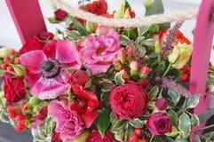 Η όμορφη floral ρύθμιση του κοκκίνου, του ροζ και burgundy ανθίζει σε ένα ρόδινο ξύλινο κιβώτιο στοκ εικόνα