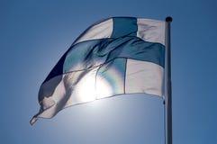 Η σημαία της Φινλανδίας αναπτύσσεται στα πλαίσια του μπλε ουρανού, τονίζεται από τον ήλιο στοκ εικόνα με δικαίωμα ελεύθερης χρήσης