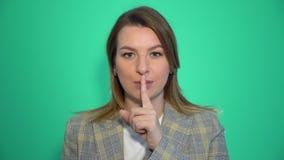 Η σιωπή, παρακαλώ κλείνει επάνω το πορτρέτο της νέας γυναίκας που κρατά το δείκτη της στα χείλια που παρουσιάζουν σημάδι σιωπής π απόθεμα βίντεο
