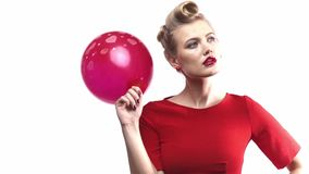 Η σκεπτόμενη ξανθή γυναίκα στο κόκκινο φόρεμα χτυπιέται με ένα μπαλόνι φιλμ μικρού μήκους