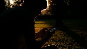 Η σκιαγραφία ενός ατόμου με ένα τηλέφωνο στα χέρια του στο ηλιοβασίλεμα, ο τύπος δακτυλογραφεί ένα μήνυμα σε ένα πακέτο στη χλόη φιλμ μικρού μήκους