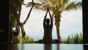 Η σκιαγραφία της γυναίκας ασκεί την περισυλλογή γιόγκας στη θέση λωτού, τεντώνει τα χέρια επάνω στην ωκεάνια παραλία, όμορφη άποψ απόθεμα βίντεο