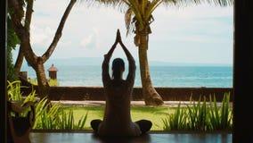 Η σκιαγραφία της γυναίκας ασκεί την περισυλλογή γιόγκας στη θέση λωτού, τεντώνει τα χέρια επάνω στην παραλία, όμορφη άποψη, ήχος  φιλμ μικρού μήκους
