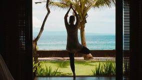 Η σκιαγραφία της γυναίκας ασκεί την περισυλλογή γιόγκας στη θέση δέντρων, τεντώνει τα χέρια επάνω στην παραλία, όμορφη άποψη, ήχο φιλμ μικρού μήκους