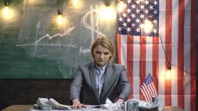 Η σοβαρή γυναίκα έντυσε στα κοστούμια με μια αμερικανική σημαία κρατώντας μια δέσμη του δολαρίου Εισοδηματικός προγραμματισμός τη απόθεμα βίντεο