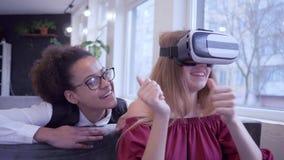 Η σύγχρονη ψυχαγωγία, γελώντας μικτά κορίτσια φίλων φυλών παίζει την εικονική πραγματικότητα χρησιμοποιώντας την ειδική κινηματογ φιλμ μικρού μήκους