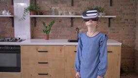 Η σύγχρονη παιδική ηλικία, μικρό κορίτσι που φορά τα γυαλιά της εικονικής πραγματικότητας παίζει στο σπίτι απόθεμα βίντεο