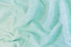 Η σύσταση μιας τσαλακωμένης πετσέτας υφασμάτων Πτυχές και παρατυπίες στο ύφασμα Πράσινο υπόβαθρο για τα σχεδιαγράμματα στοκ εικόνα