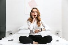 Η συγκλονισμένη επιχειρησιακή γυναίκα έντυσε στο επίσημο πουκάμισο ενδυμάτων καθμένος στο εσωτερικό στο κρεβάτι εξετάζοντας το ρο στοκ φωτογραφίες με δικαίωμα ελεύθερης χρήσης