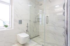 Η τουαλέτα και η λεπτομέρεια ενός μπιντέ ντους γωνιών με τους διανομείς σαπουνιών και σαμπουάν στον τοίχο τοποθετούν τη σύνδεση ν στοκ εικόνες
