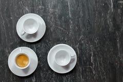 Η τοπ άποψη σχετικά με τρία λίγος καφές κοιλαίνει στο ιώδες μαρμάρινο υπόβαθρο Ένας με τον καφέ, δύο άλλοι κενοί στοκ φωτογραφία