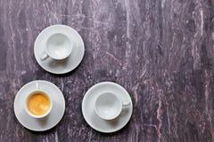 Η τοπ άποψη σχετικά με τρία λίγος καφές κοιλαίνει στο ιώδες μαρμάρινο υπόβαθρο Ένας με τον καφέ, δύο άλλοι κενοί στοκ εικόνες με δικαίωμα ελεύθερης χρήσης