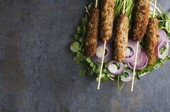 Η τοπ άποψη του kebab με τα δαχτυλίδια κρεμμυδιών, φρέσκο cilantro εξυπηρέτησε στο σκοτεινό πίνακα Κενό διάστημα στοκ φωτογραφία με δικαίωμα ελεύθερης χρήσης