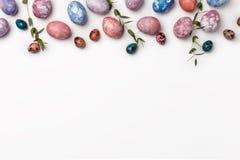 Η τοπ άποψη των αυγών Πάσχας χρωμάτισε με το μπλε, ρόδινο και πορφυρό χρώμα στα διαφορετικά σχέδια με τις εγκαταστάσεις Άσπρη ανα στοκ εικόνα με δικαίωμα ελεύθερης χρήσης