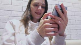 Η χαμογελώντας γυναίκα δακτυλογραφεί ένα μήνυμα στην κινητές τηλεφωνικές συνεδρίαση και την αναμονή κάποιος στον καφέ απόθεμα βίντεο