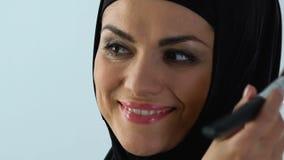 Η χαμογελώντας μουσουλμανική γυναίκα στη δεκαετία του '30 της που εφαρμόζει το πρόσωπο κοκκινίζει, καλλυντικά αντι-ηλικίας, σύνθε φιλμ μικρού μήκους