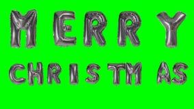 Η Χαρούμενα Χριστούγεννα λέξης που χαιρετά από το ήλιο ασημώνει τις επιστολές μπαλονιών που επιπλέουν στην πράσινη οθόνη - φιλμ μικρού μήκους