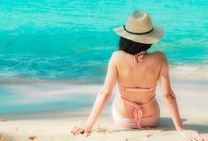 Η πίσω άποψη της ευτυχούς νέας ασιατικής γυναίκας στο ρόδινο καπέλο μαγιό και αχύρου χαλαρώνει και απολαμβάνει τις διακοπές στην  στοκ εικόνες