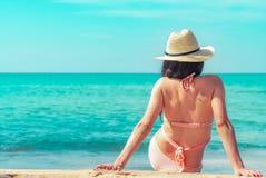 Η πίσω άποψη της ευτυχούς νέας ασιατικής γυναίκας στο ρόδινο καπέλο μαγιό και αχύρου χαλαρώνει και απολαμβάνει τις διακοπές στην  στοκ εικόνες με δικαίωμα ελεύθερης χρήσης