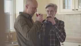 Η παλαιά στάση ζευγών στην κουζίνα με το γυαλί κρασιού σε τους χέρια, γυναίκα προσπαθεί να ηρεμήσει κάτω και να χαλαρώσει τον άνδ απόθεμα βίντεο