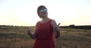 Η πανέμορφη γυναίκα στα γυαλιά ηλίου και ένα κόκκινο ντύνουν το χορό σε έναν τομέα στην slo-Mo απόθεμα βίντεο