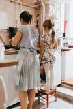 Η παραμονή μικρών κοριτσιών στο σκαμνί δίπλα στη μητέρα της μαγειρεύει τις τηγανίτες για το πρόγευμα στη μικρή άνετη κουζίνα στοκ εικόνα με δικαίωμα ελεύθερης χρήσης
