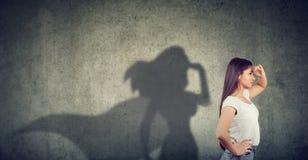 Η πλάγια όψη μιας γυναίκας που φαντάζεται για να είναι ένας έξοχος ήρωας που κοιτάζει επεδίωξε στοκ φωτογραφία
