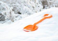 Η πορτοκαλιά πλαστική λεπίδα των παιδιών βρίσκεται snowdrift το χειμώνα στοκ φωτογραφία με δικαίωμα ελεύθερης χρήσης