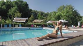 Η προκλητική σγουρή γυναίκα κάνει ηλιοθεραπεία στην άκρη της λίμνης απόθεμα βίντεο