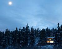 Θερμά φω'τα του άνετου σπιτιού σε δασικό Yukon Καναδάς στοκ φωτογραφίες