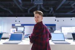 Θετικός νεαρός άνδρας στο τμήμα υπολογιστών του καταστήματος ηλεκτρονικής στοκ φωτογραφίες με δικαίωμα ελεύθερης χρήσης