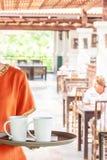 Θηλυκή σερβιτόρα που κρατά έναν δίσκο των φλυτζανιών καφέ στο εσωτερικό ενός θερινού υπαίθριου εστιατορίου Παραλία LAK Khao, Phan στοκ εικόνες με δικαίωμα ελεύθερης χρήσης