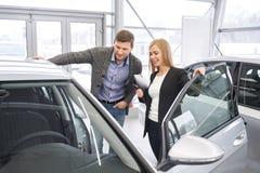 Θηλυκός έμπορος αυτοκινήτων που παρουσιάζει αυτοκίνητο στον πιθανό αγοραστή στοκ εικόνες