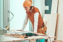 Θηλυκός ξυλουργός με την τοποθέτηση κορδελών στο εργαστήριο ξυλουργικής στοκ φωτογραφία